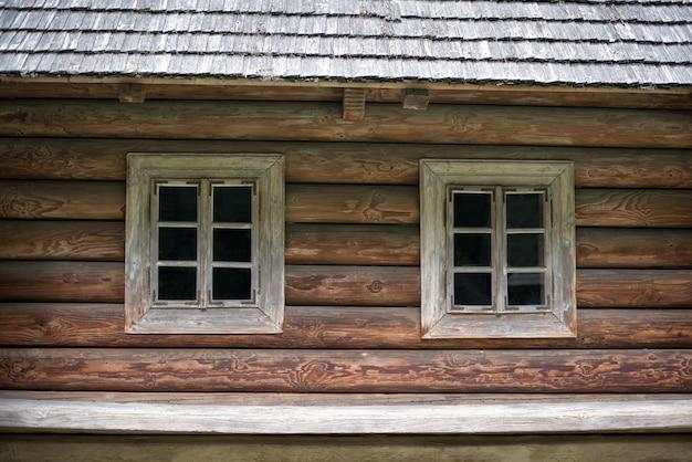 Casa de madeira velha com duas janelas. casa na zona rural. rústico. Foto Premium