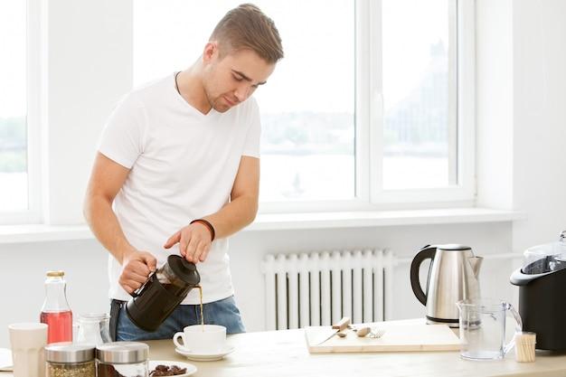 Casa de manhã. homem com copo de café Foto gratuita