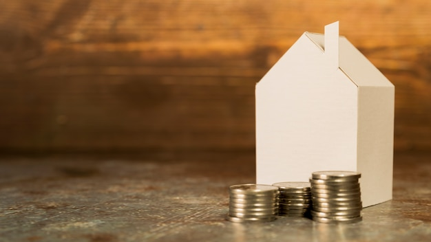 Casa de papel em miniatura com pilha de moedas no chão contra o pano de fundo de madeira Foto gratuita