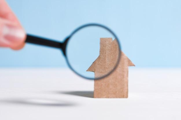 Casa de papelão abstrata, mão segura uma lupa de vidro. verificar a casa, a legalidade da transação. Foto Premium