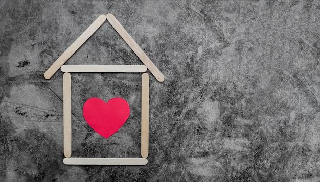 Casa de paus de madeira criativa sorvete com coração vermelho em uma parede velha Foto gratuita