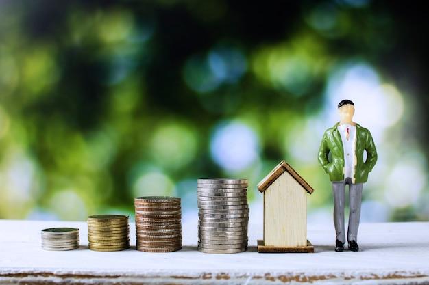 Casa e conceito imobiliário, homem de negócios permanente com empilhados de moedas e casa Foto Premium