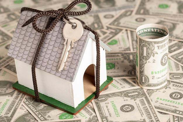 Casa embrulhada com chaves em fundo de dinheiro Foto gratuita