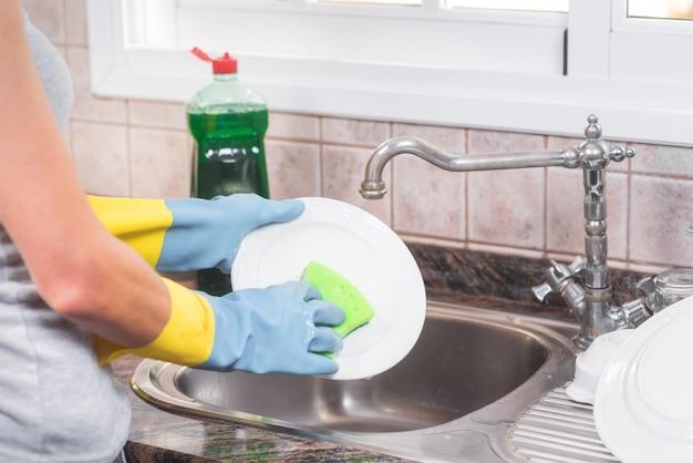 Casa esposa lavar pratos na cozinha Foto Premium