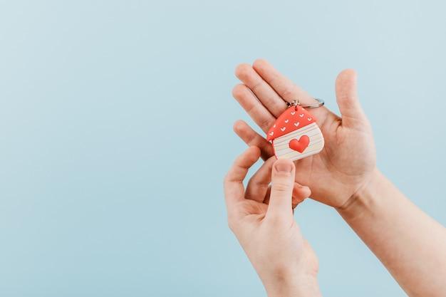 Casa figura com um coração vermelho na mão de crianças Foto Premium