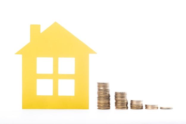 Casa imobiliária e pilhas de moedas no fundo branco Foto gratuita