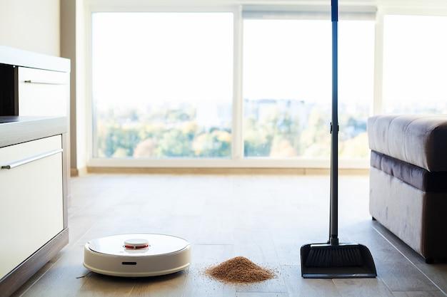 Casa inteligente, aspirador de pó robô executa a limpeza automática do apartamento em um determinado momento Foto Premium