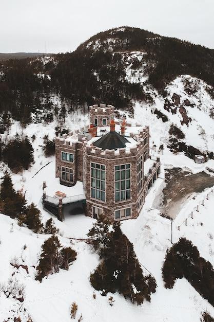 Casa marrom e branca no chão coberto de neve Foto gratuita