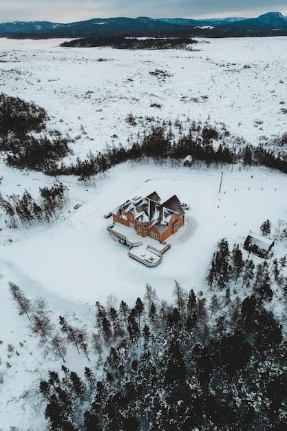 Casa marrom e preta no campo de neve ao lado de árvores durante o dia Foto gratuita