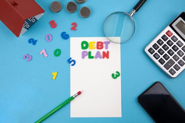 Casa modelo, calculadora, moedas, lupa com a palavra plano de dívida Foto Premium