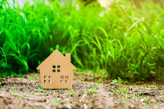 Casa modelo pequena no campo de grama verde. - família, imóveis ou empréstimo para o conceito de investimento empresarial. Foto Premium