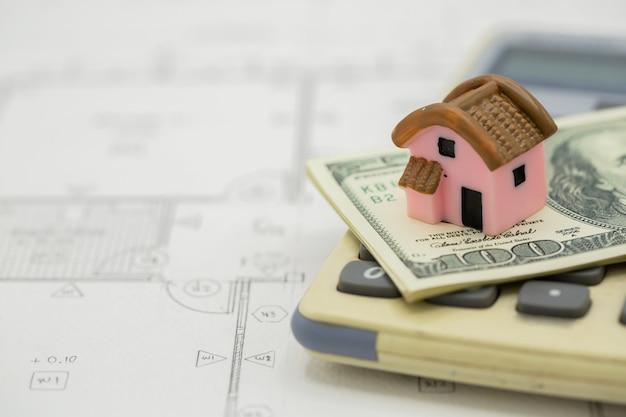 Casa na calculadora com notas de dólar Foto gratuita