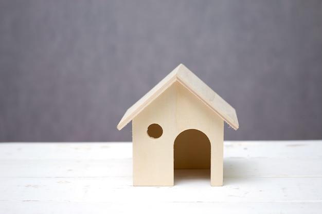 Casa ou casa de madeira do brinquedo no fundo branco do cinza da tabela. Foto Premium