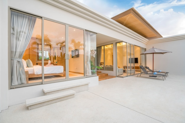 Casa ou casa design exterior mostrando villa piscina tropical com cama de sol Foto Premium