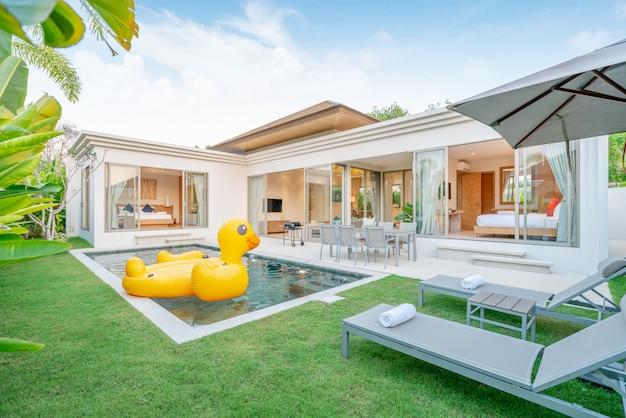 Casa ou casa design exterior mostrando villa piscina tropical com jardim de verdura, cama de sol e pato flutuante Foto Premium