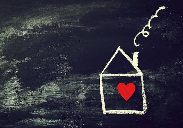 Casa ou conceito amor. casa pintada com coração vermelho em um ch preto Foto gratuita