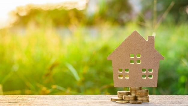Casa pequena e uma pilha de moedas de ouro no jardim Foto Premium