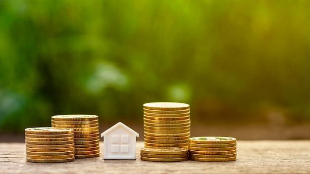 Casa pequena e uma pilha de moedas douradas no jardim. Foto Premium