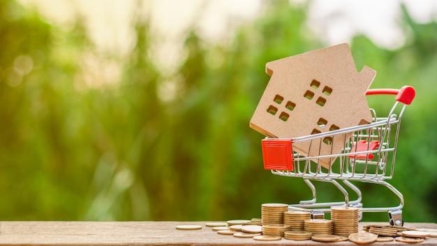 Casa pequena em um carrinho de compras e uma pilha de moedas douradas na tabela de madeira. Foto Premium