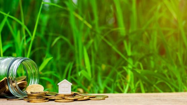 Casa pequena na pilha de moedas de ouro no jardim Foto Premium