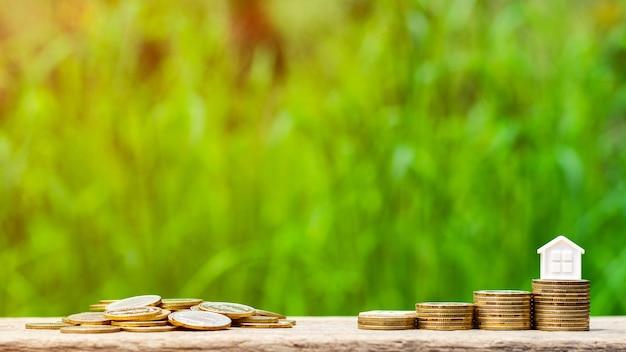 Casa pequena na pilha de moedas douradas no jardim. - conceito de propriedade de investimento. Foto Premium