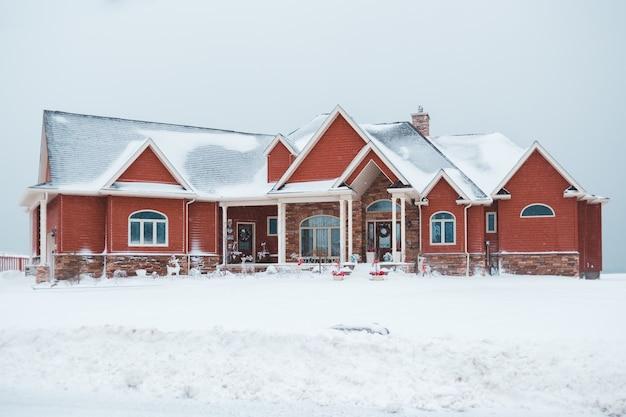Casa vermelha e cinza durante a neve Foto gratuita