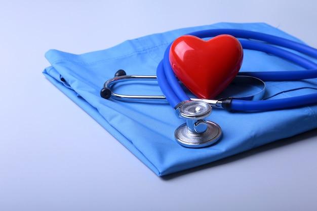 Casaco médico com estetoscópio médico e coração vermelho na mesa Foto Premium