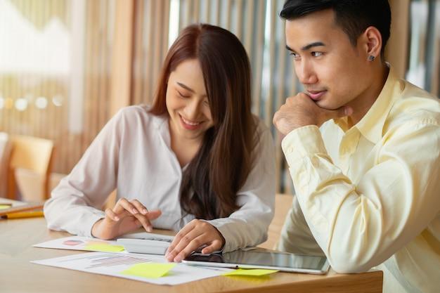 Casais asiáticos estão calculando receitas e despesas para cortar despesas desnecessárias e planejando pedir dinheiro emprestado para comprar uma nova casa. conceitos para planejamento de investimentos e planejamento financeiro para a família Foto Premium