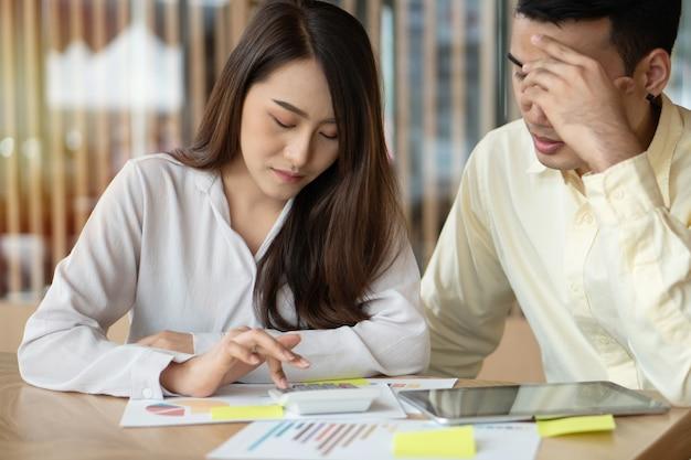 Casais asiáticos infelizes estão calculando receitas e despesas para cortar despesas desnecessárias. Foto Premium