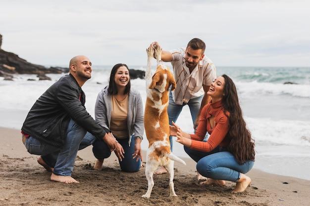 Casais com cachorro na beira-mar Foto gratuita