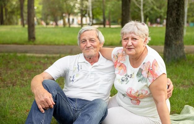 Casais de idosos caucasianos sentam e relaxam no parque. casal sênior se divertindo e se abraçando. Foto Premium