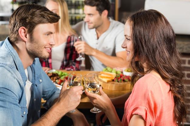 Casais felizes bebendo vinho branco Foto Premium