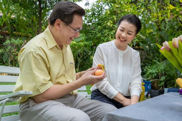 Casais idosos asiáticos estão cuidando uns dos outros, tirando laranjas para comer. conceito de família, conceito de casais Foto Premium