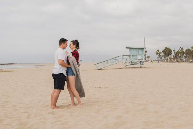 Casal abraçados na praia e posando Foto gratuita