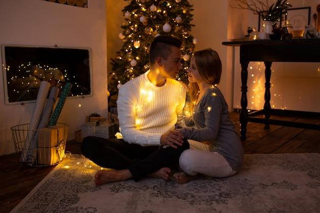 Casal abraçando em casa na época do natal Foto Premium