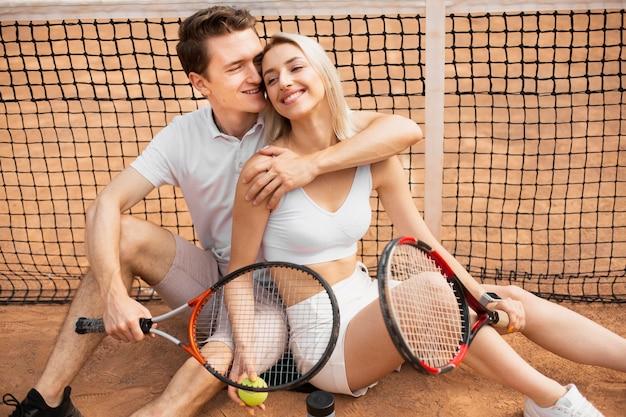 Casal abraçando na quadra de tênis Foto gratuita