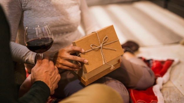 Casal abrindo presentes junto com copo de vinho Foto gratuita