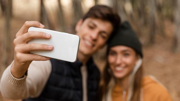 Casal acampando e tirando uma foto Foto Premium