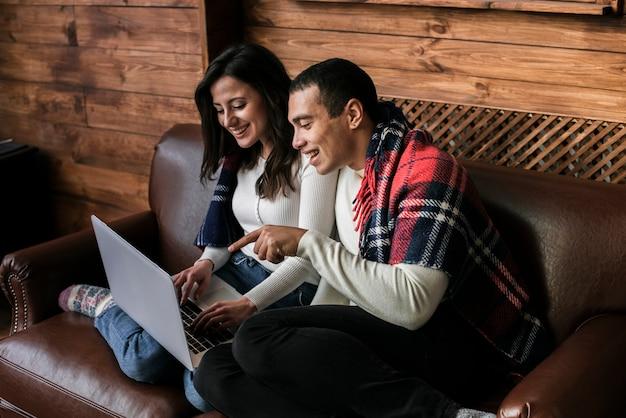 Casal adorável, juntamente com um laptop Foto gratuita