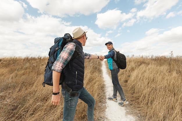 Casal adulto com mochilas na natureza Foto gratuita