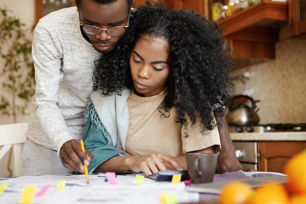 Casal africano estressado com muitas dívidas, cuidando da papelada em casa. homem sério de óculos usando lápis apontando para um pedaço de papel na mesa, enquanto sua jovem esposa faz cálculos na calculadora Foto gratuita