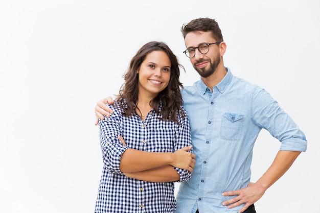 Casal alegre, abraçando e posando Foto gratuita