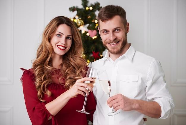 Casal alegre brindando champanhe Foto gratuita