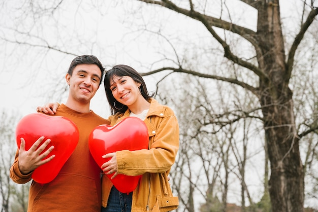Casal alegre com balões em forma de coração Foto gratuita