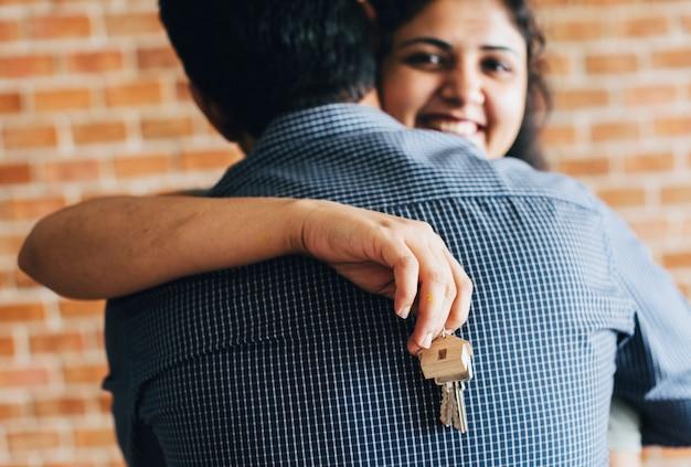 Casal alegre com chaves para sua nova casa Foto gratuita
