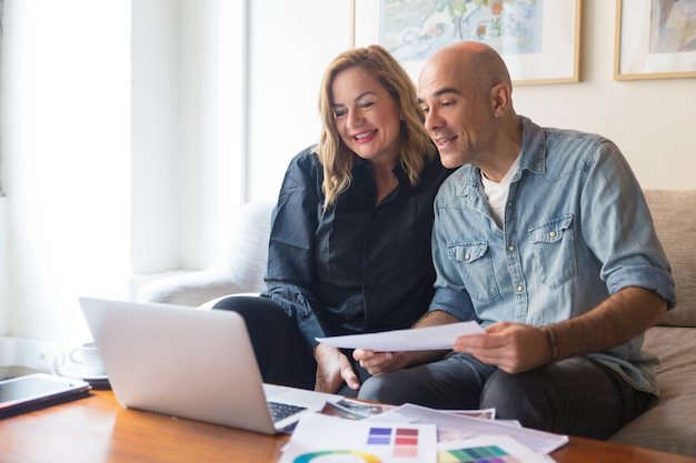 Casal alegre de clientes consultoria designer de interiores Foto gratuita