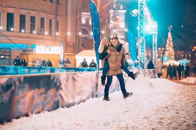 Casal alegre e brincalhão em roupas de inverno quente estão brincando Foto gratuita