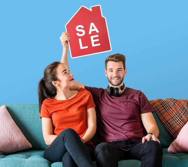 Casal alegre, segurando um ícone de venda de casa Foto gratuita