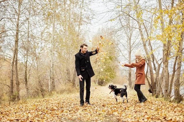 Casal andando com o cão no parque e abraçando Foto Premium