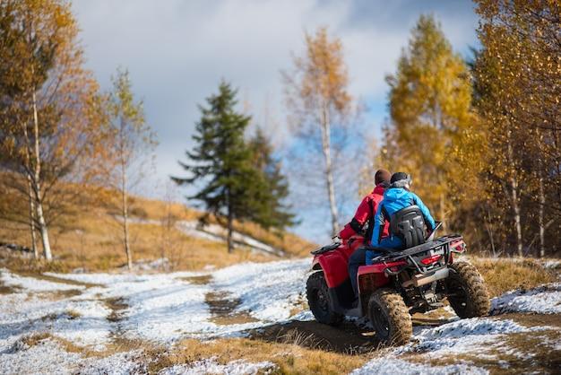 Casal andando em quad bike na estrada coberta de neve Foto Premium
